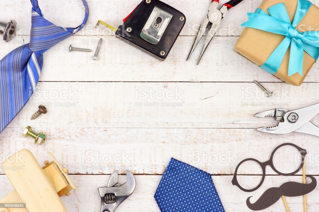 Fathers Day frame of gifts, decor, ties and tools on white wood stock photo