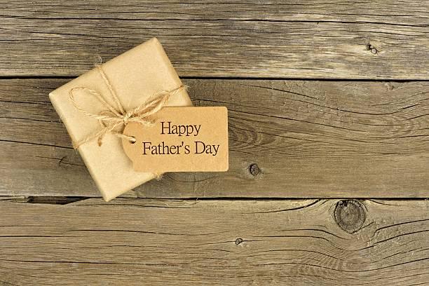 vatertags-geschenk-box mit etikett auf rustikal holz - vatertagsgrüße stock-fotos und bilder