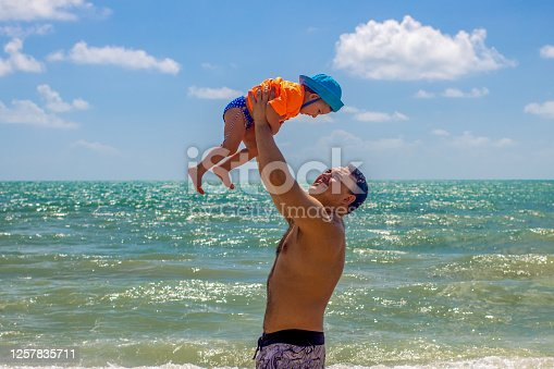 father's day. happy dad holds a cheerful little baby above him. background of the sandy seashore.