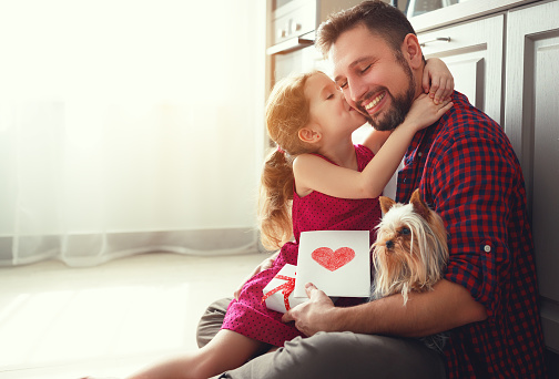 istock Father's day. Happy family daughter giving dad greeting card 943968298
