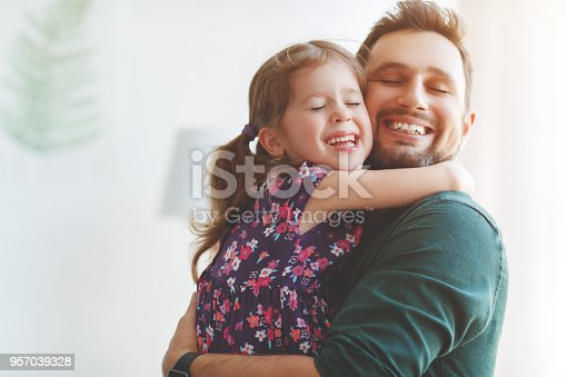 istock Father's day. Happy family daughter hugs his dad 957039328