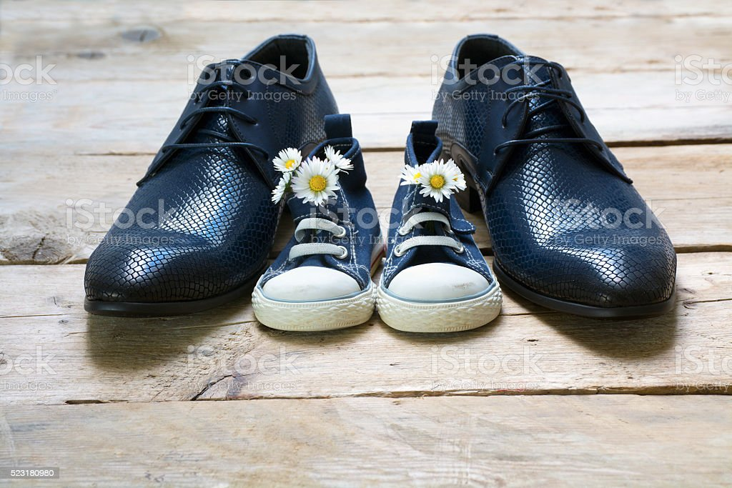 Father's day, kids sneakers with daisies between men's shoes stock photo