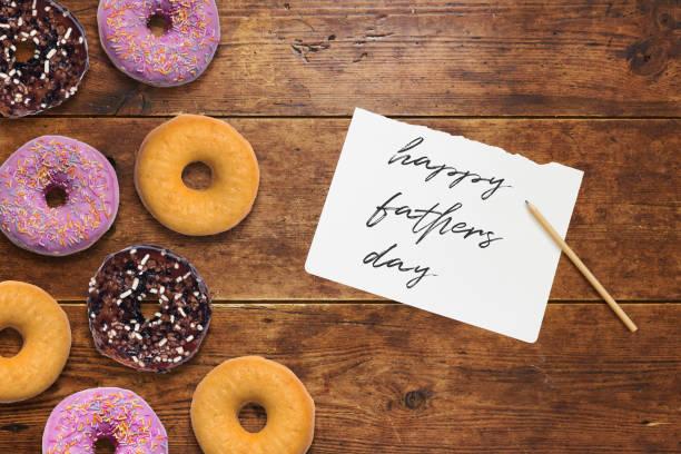 vatertag-hinweis zu papa mit bunten donuts - vatertagsgrüße stock-fotos und bilder