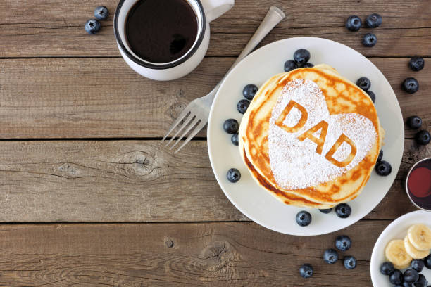 Fathers Day pancake breakfast with heart shape and DAD letters, above view corner border on rustic wood stock photo
