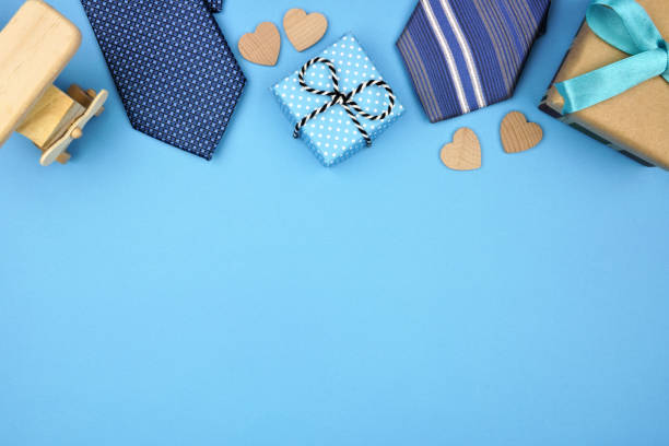 Fathers Day top border of gifts, ties and hearts on a blue background stock photo