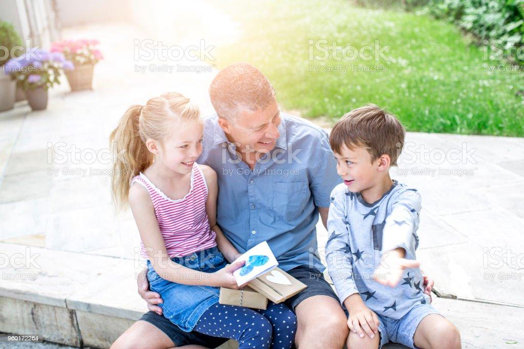 Väterlichen Tag - zwei Kinder beschenken ihre lächelnden Vater – Foto