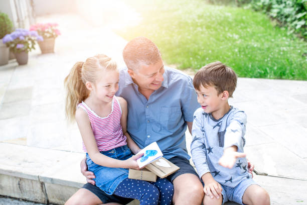 father´s day - two children give gifts to their smiling father - fathers day stock photos and pictures
