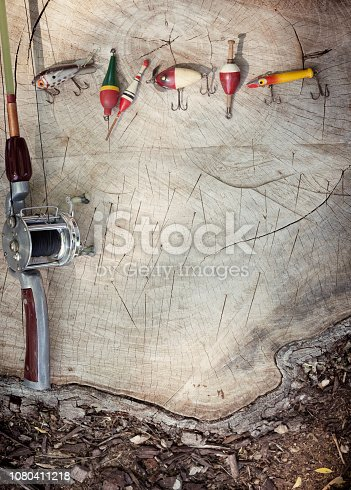 Father's Day Concept: Vintage fishing rod, reel, line and lures on an old wood tree stump background