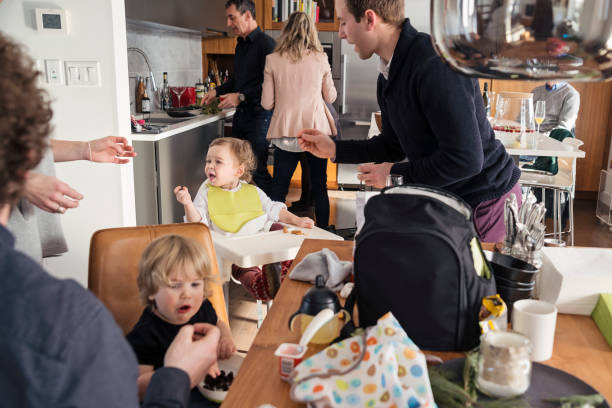 fathers feeding toddlers before big family dinner, lots of action. - busy stock photos and pictures