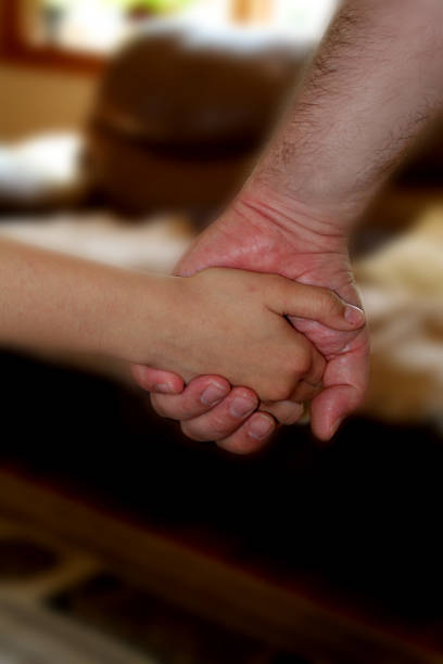 Father's hand holding child's hand stock photo