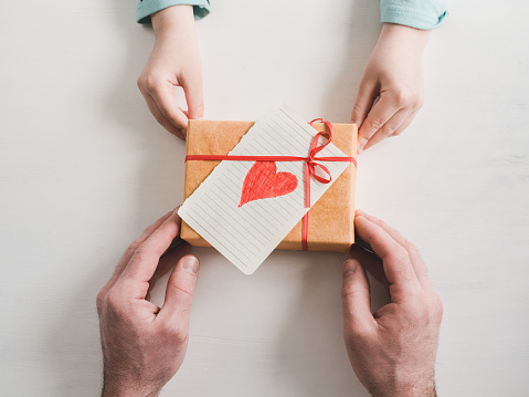 Beautiful box with a gift, a red ribbon, a card with a heart, a loving father's hands and the youngest daughter on a white background. View from above. Preparation for Father's Day