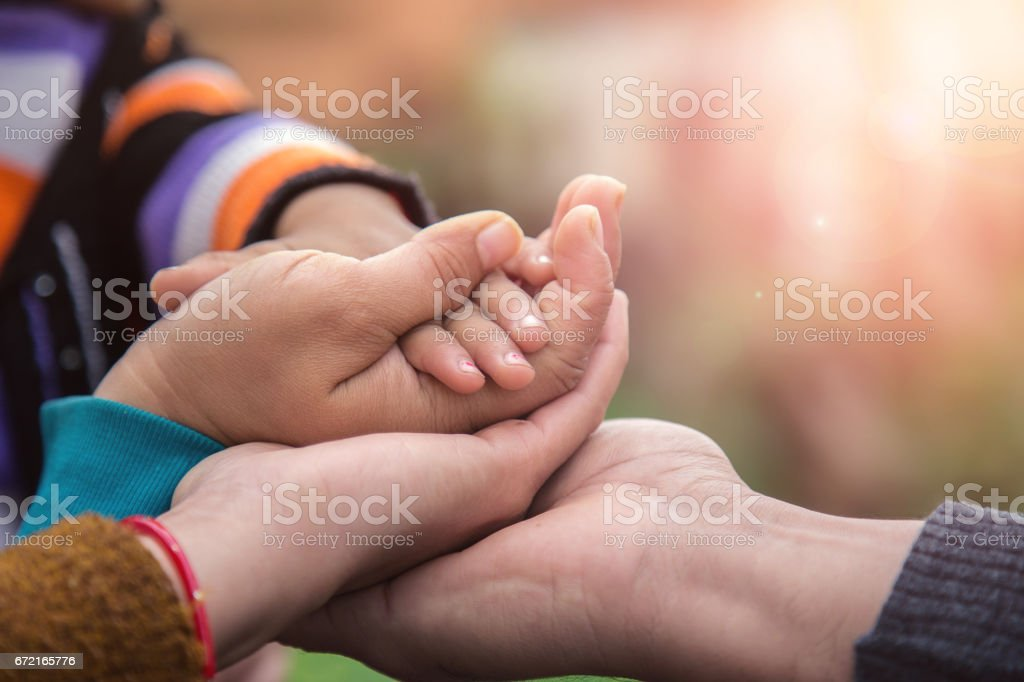 Father's mother's and baby's hand stock photo
