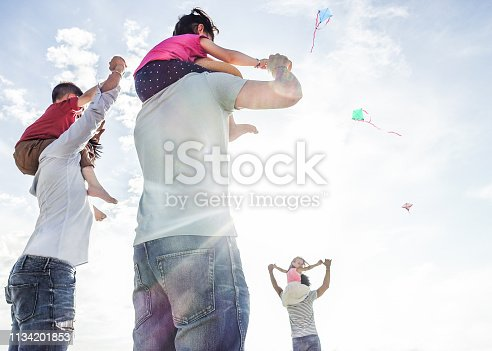 453383283 istock photo Fathers with children flying with kites and having fun on the beach - Families friends playing with sons on summer vacation - Travel and holidays concept - Focus on center man body - Warm filter 1134201853