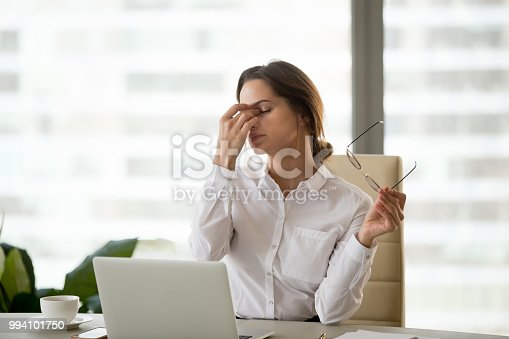 istock Fatigued businesswoman taking off glasses tired of computer work 994101750