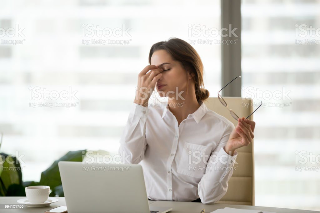 Fatigued businesswoman taking off glasses tired of computer work stock photo