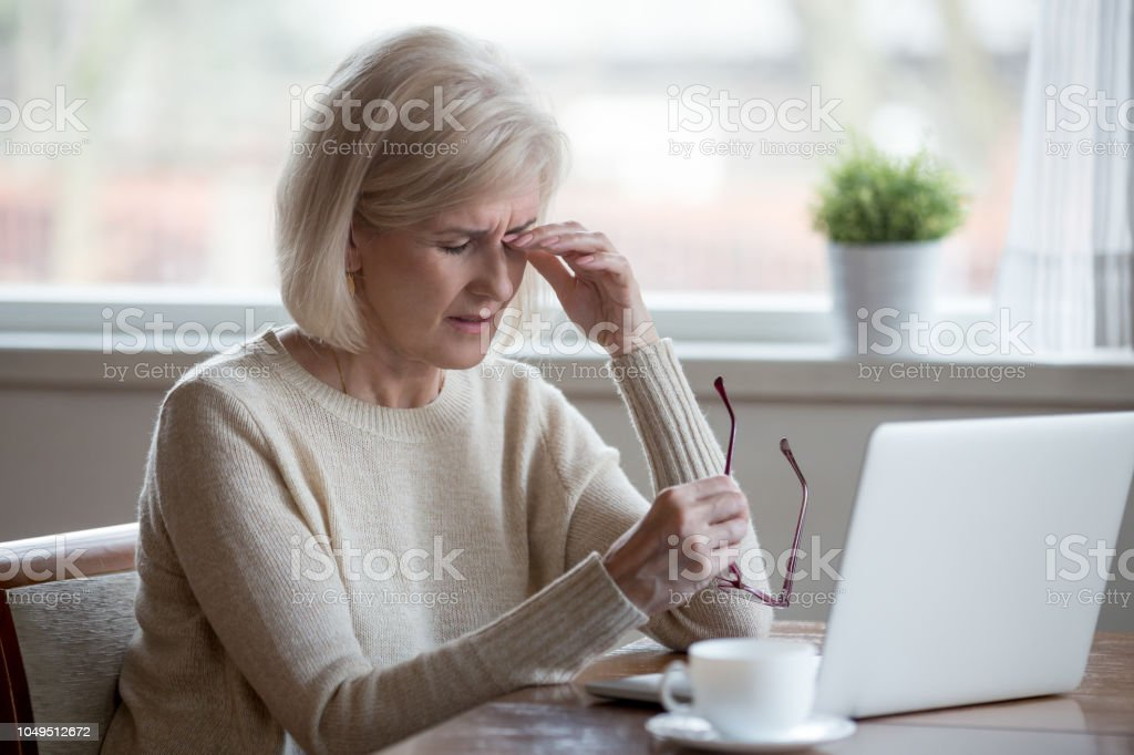 Fatigued mature woman taking off glasses suffering from eye strain stock photo