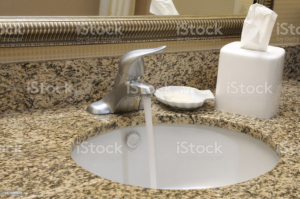 Faucet and bathroom sink with granite countertop royalty-free stock photo