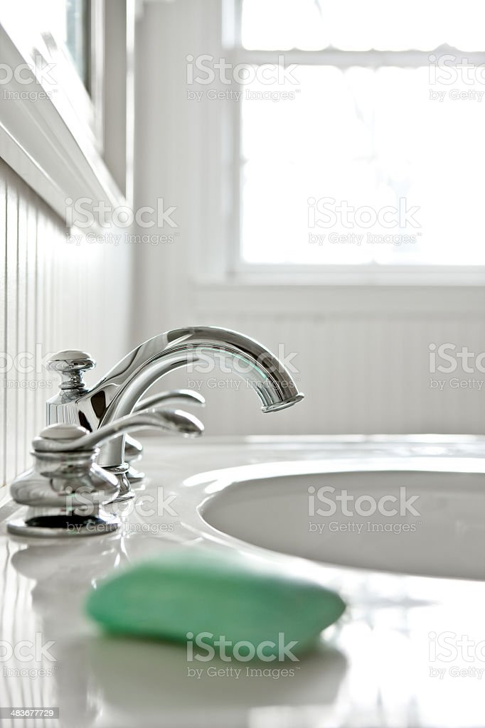 Faucet in  white bathroom with a bar of soap. royalty-free stock photo