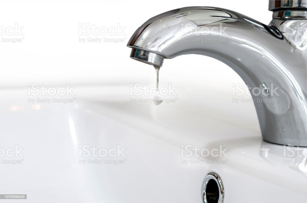 Faucet with a drop of water against a white sink. Water leaking and...