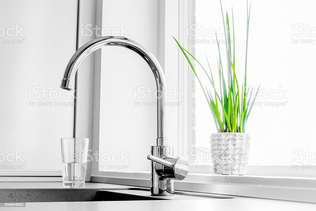 Faucet with a green plant stock photo