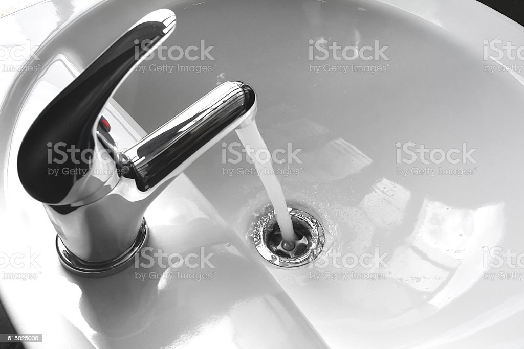Faucet with Running Water in a Sink stock photo