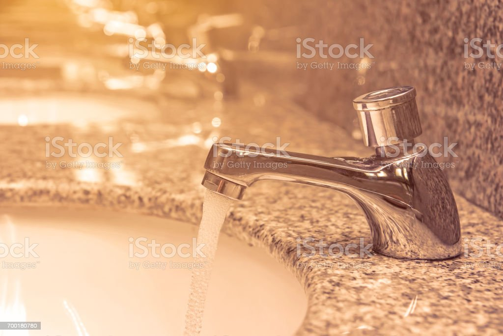 faucet with water flow on sink in luxury bathroom stock photo