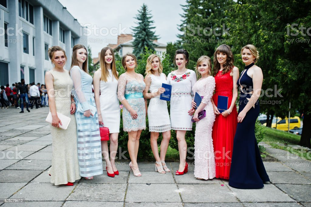 Faulous young women graduates in chic evening gowns posing outside in the park. stock photo