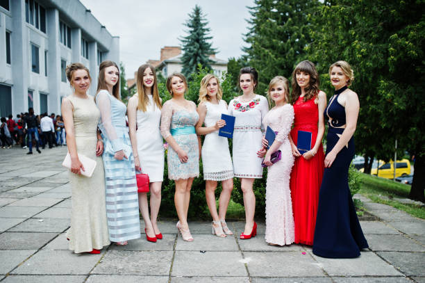 faulous young women graduates in chic evening gowns posing outside in the park. - prom stock photos and pictures