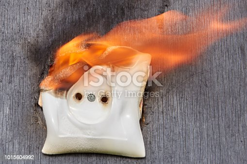 istock Faulty wiring, flame in room, ignition of power supply socket. 1015604992