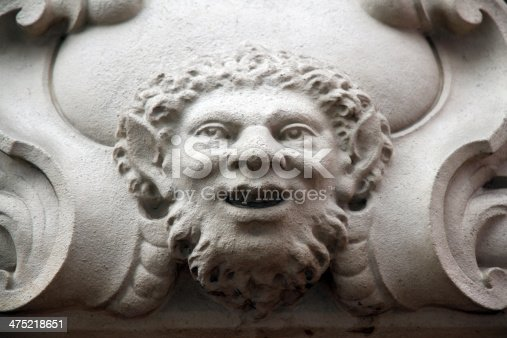 A faun gargoyle in Paris. the face is part of the carvings above the entrance to a Parisian apartment block.
