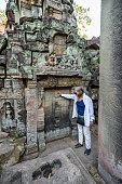 Siem Reap, Cambodia - January 21, 2020: Lone female tourist is pointing at faux door at Preah Khan temple. Preah Khan is a temple at Angkor, Cambodia, built in the 12th century by King Jayavarman VII to honor his father. It is left largely unrestored, with numerous trees and other vegetation growing among the ruins.