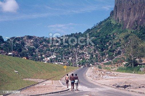 Rio de Janeiro, Brazil, 1973. Favela beside a rock near Rio de Janeiro. Furthermore: pedestrians, road and small huts.