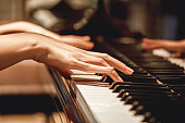 Favorite classical music...Close up view of gentle female hands playing a melody on piano while taking piano lessons. Musical instrument. Music education. Piano keyboard