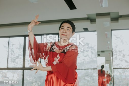 Medium shot of confident grandmother  enjoy showing and resting with classical Thai dance at home, Bangkok Thailand