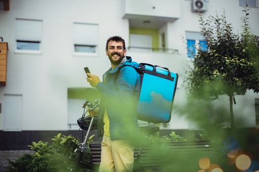A scene depicting a man during his daily routine as a courier. He's happily preparing to drop off the next delivery.