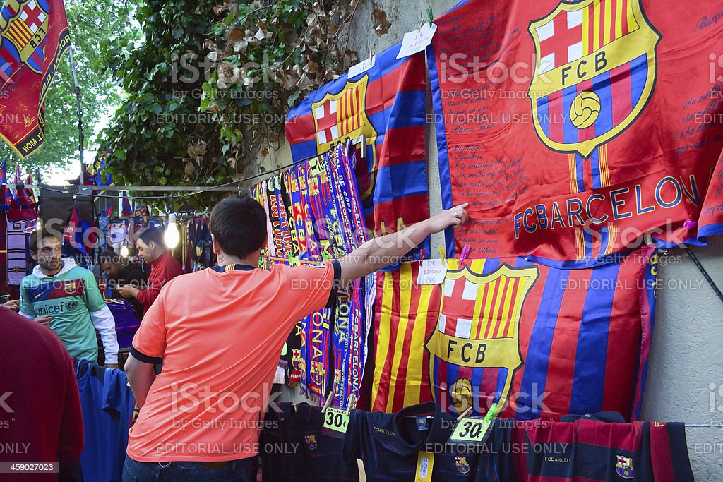 """fc barcelona shop """"Barcelona, Spain-april 21, 2012 :man is showing by his hand to the flag of FC Barcelona at the street shop, situated close to the stadium Camp Nou in Barcelona"""" Adult Stock Photo"""