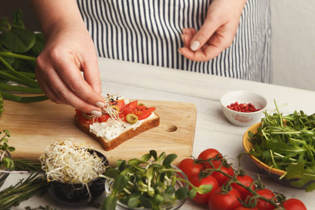 Feamale hands making healthy bruschettas for right snack Cooking healthy vegetarian sandwiches. Female hands making whole grain bruschetta with avocado topping, juicy cherry tomatoes and microgreen. Eating right concept female sandwich stock pictures, royalty-free photos & images