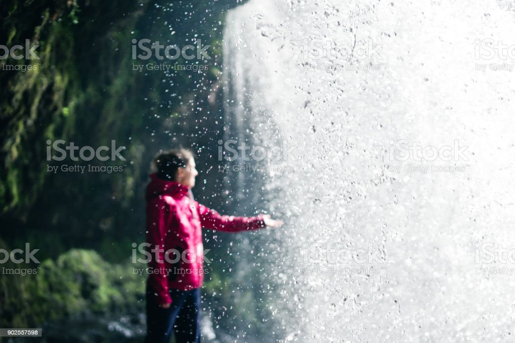 Feamale hiker, tourist, model out of focus touching water under the Sgwd Yr Eira Waterfall in Wales stock photo