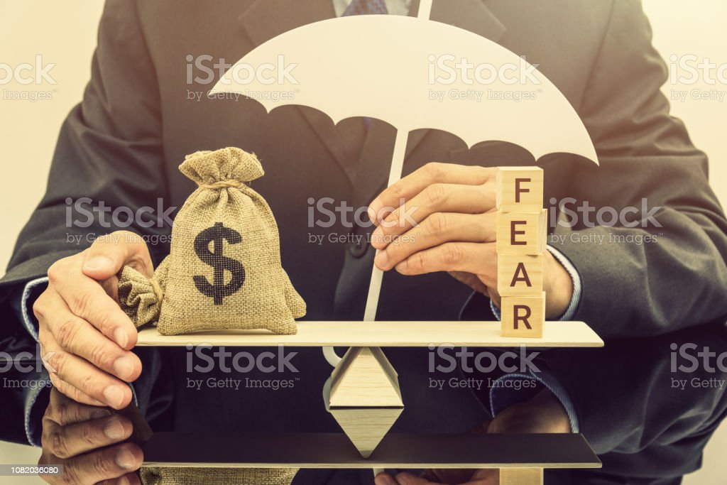 Fear and greed or anxiety in financial market concept : Businessman carries a white umbrella, protects dollar bags or properties on basic balance scale, depicts the influence of emotions on investors stock photo