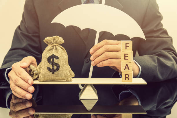 Fear and greed or anxiety in financial market concept : Businessman carries a white umbrella, protects dollar bags or properties on basic balance scale, depicts the influence of emotions on investors Fear and greed or anxiety in financial market concept : Businessman carries a white umbrella, protects dollar bags or properties on basic balance scale, depicts the influence of emotions on investors greed stock pictures, royalty-free photos & images