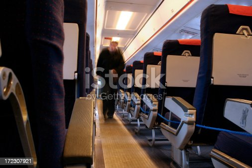 A motion blurred figure walks up the aisle of an empty aircraft