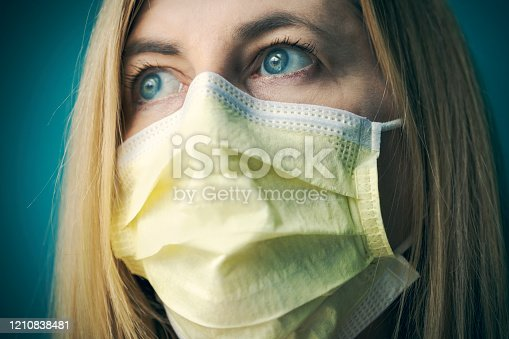 A close up of a woman in her 40's fearful of catching a virus and wearing a face protection mask.