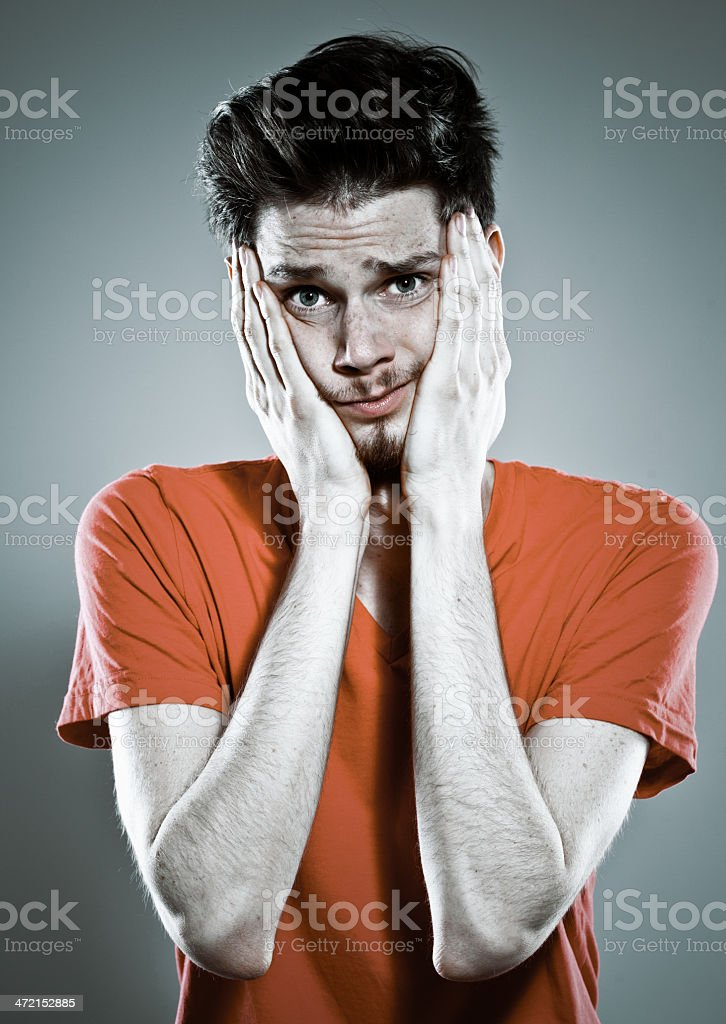 Fear Portrait of worried young man staring at camera with hand on his face. Studio shot, grey background. 20-29 Years Stock Photo