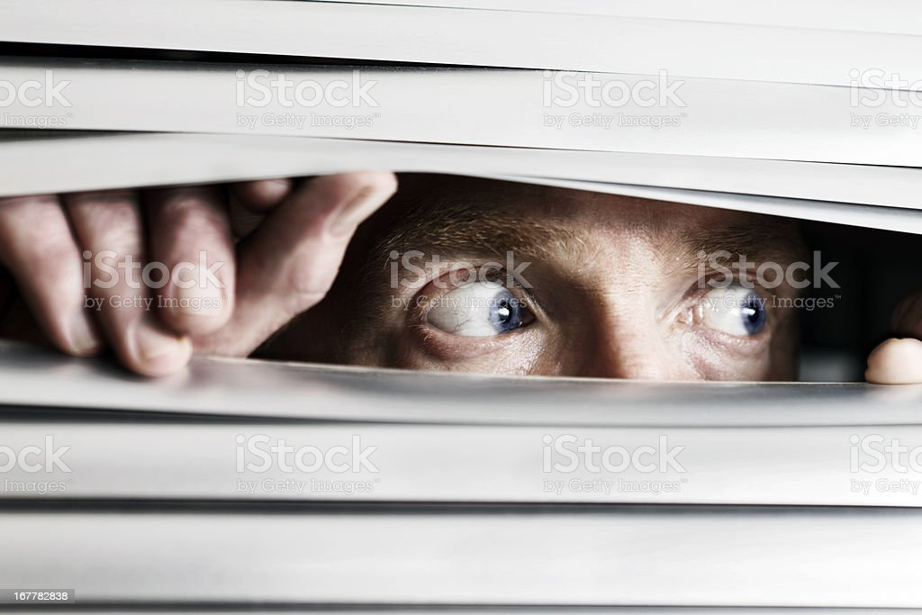 Fearful man looking sideways through venetian blind stock photo