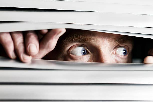 hombre temible vista de costado a ciego veneciano - conspiración fotografías e imágenes de stock