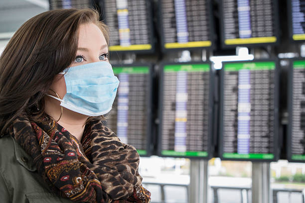 Fearful Passenger Wears Mask at the Airport An attractive female wears a mask at the airport, possibly fearful of Ebola. pandemic illness stock pictures, royalty-free photos & images