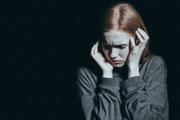 Fearful woman covering her ears Fearful woman covering her ears, vitctim of domestic violence hands covering ears stock pictures, royalty-free photos & images
