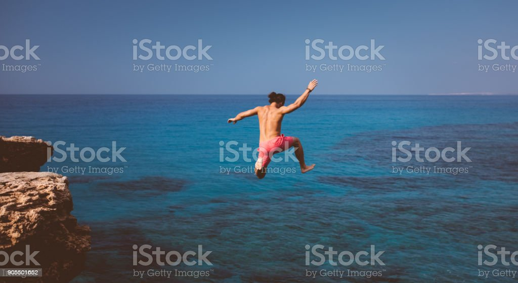 Fearless cliff diver diving into tropical island sea stock photo