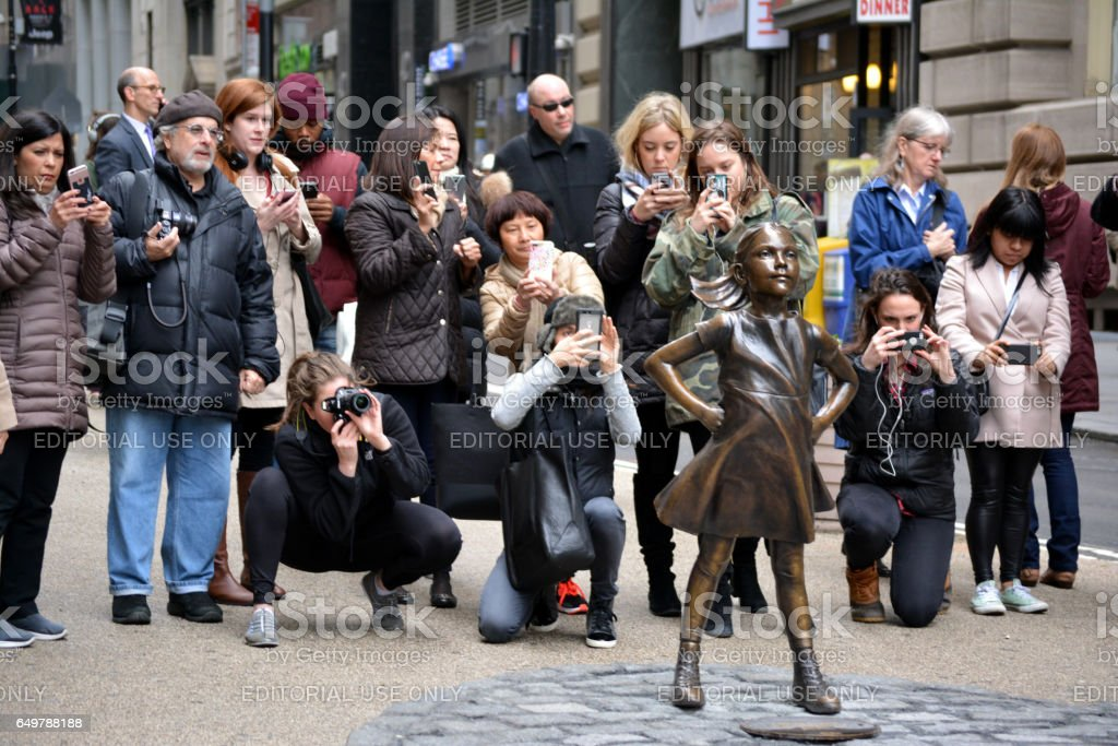 """Fearless Girl People gathering around """"The Fearless Girl"""" statue placed in Lower Manhattan to help mark International Women's Day. Battle of The Sexes - Concept Stock Photo"""