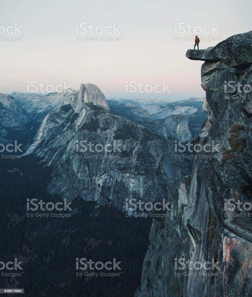 A fearless hiker is standing on an overhanging rock enjoying the view towards famous Half Dome at Glacier Point, Yosemite National Park, California, USA stock photo